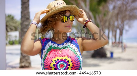 Pretty adult female in reflective yellow sunglasses standing outside on tropical beach adjusting her hat - stock photo