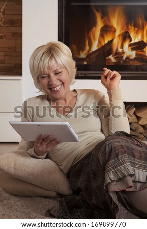 Pretty adult female using digital tablet computer by fireplace, looking down, hearty laughing  - stock photo