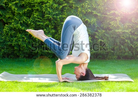 pretty adult woman doing yoga on a green grass at summer day - stock photo