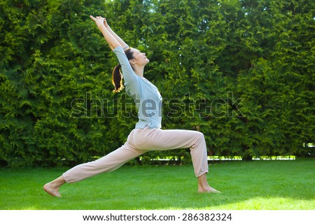 pretty adult woman doing yoga on the green grass in the park - stock photo
