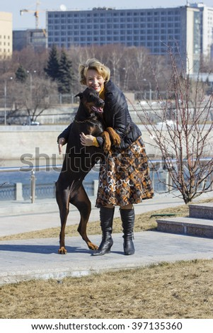 Pretty adult woman playing with her doberman female dog outdoors - stock photo