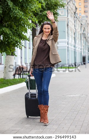pretty adult woman traveler with suitcase walking along the platform, smiling and waving his hand