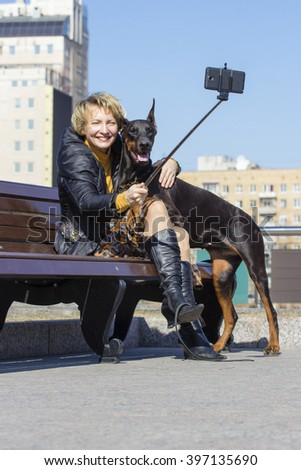 Pretty adult woman with dog outdoors - stock photo