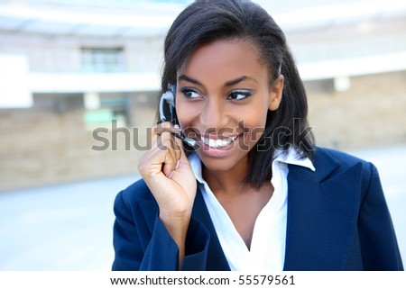 Pretty african american business woman talking on ear phone at office building