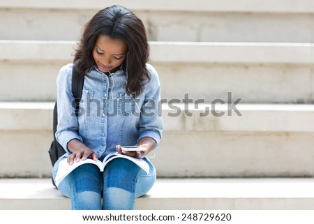 pretty african american college student reading a book - stock photo