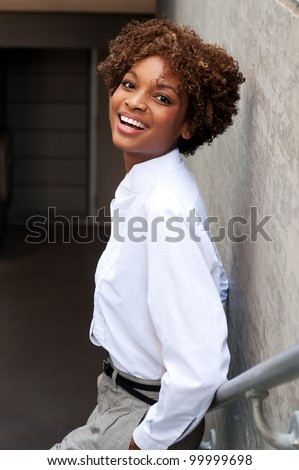 pretty African American executive standing outside with hands in pockets - stock photo