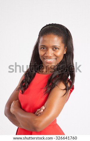 Pretty African American girl in a red dress,  smiling with her arms crossed