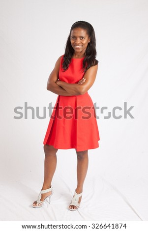 Pretty African American girl in a red dress,  smiling with her arms folded - stock photo