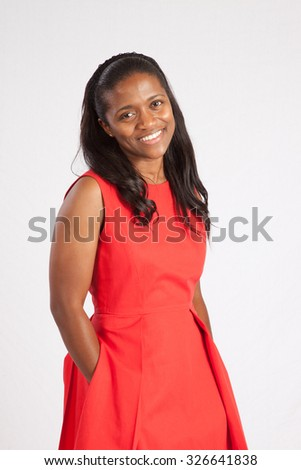 Pretty African American girl in a red dress,  smiling with her hands in her pockets - stock photo