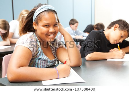 Pretty African-American girl in diverse middle school class. - stock photo