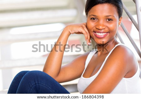 pretty african american girl sitting alone on steps - stock photo