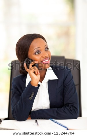 pretty african american office worker talking on cell phone - stock photo