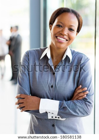 pretty african american office worker with arms crossed - stock photo