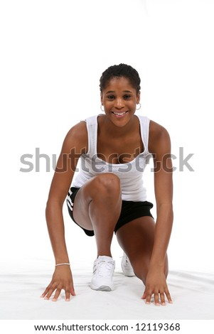 Pretty African American teenage girl, posing in runners starting position and smiling. - stock photo