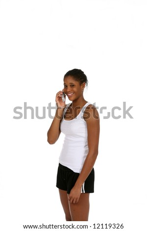 Pretty African American teenage girl wearing athletic shorts and a tank top, talking on a cell phone. - stock photo