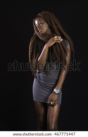 Pretty African American woman with long dreadlocks, looking thoughtful