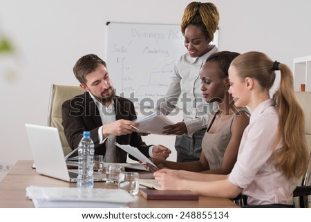 Pretty african businesswoman explaining strategy to colleagues at meeting - stock photo