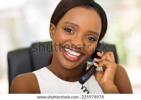 pretty african businesswoman using landline phone - stock photo