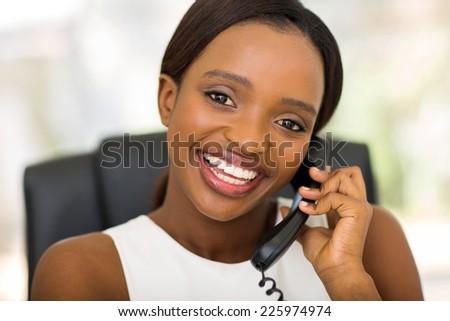 pretty african businesswoman using landline phone - stock photo
