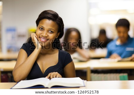 pretty african college student reading book in library - stock photo