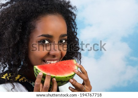 Pretty African Ethiopian girl eating a juicy watermelon - stock photo