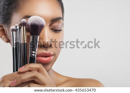 Pretty african girl is doing facial make-up