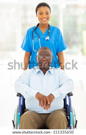 pretty african health care worker and disabled senior patient  - stock photo