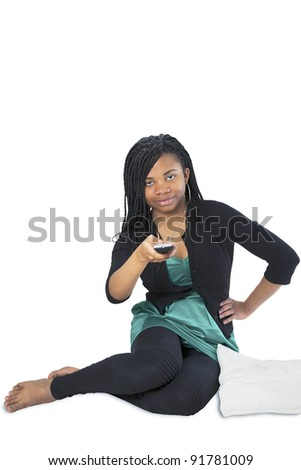 Pretty african teenager changing TV channel with remote control - stock photo