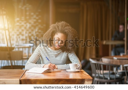 Pretty african woman is learning subject in cafeteria - stock photo