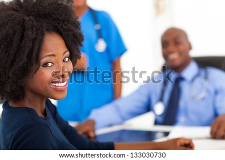 pretty african woman visiting her doctor in office - stock photo