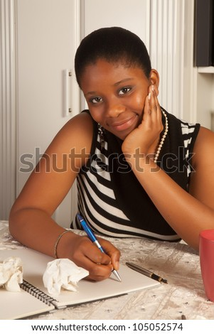 Pretty african woman writing a letter at home - stock photo