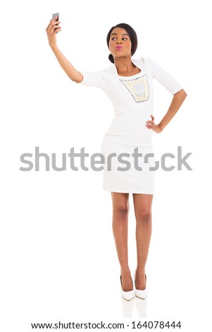 pretty afro american woman taking self portrait using smart phone on white background - stock photo