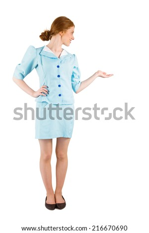 Pretty air hostess presenting with hand on white background - stock photo