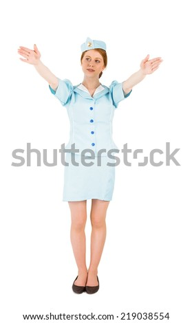 Pretty air hostess with arms raised on white background