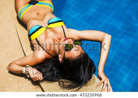 Pretty amazing luxurious brunette lying near the pool, enjoying the sun, perfect figure, tanned healthy skin, long hair, red lips, bright bikini, sunglasses, top view, trendy accessories, gold jewelry - stock photo