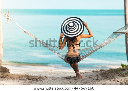 Pretty amazing luxury Tanned young girl on the beach, sitting in a hammock with his back to the camera and looking at the sea, ocean, black sexy bikini, wide striped hat, lifestyle - stock photo