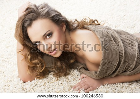 pretty and attractive young brunette in a warm brown sweater laying down on a white carpet, she looks in to the lens with sensual expression,  her right hand is near the face and the left hand is on