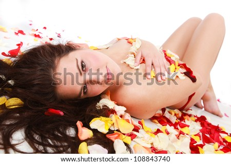 Pretty and beautiful brunette woman lying on white isolated background surrounded by red orange and yellow rose petals - stock photo