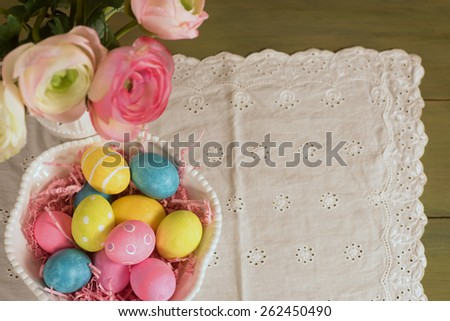 Pretty and Bright, Colorful Easter Eggs in a Bowl on White Tablecloth with Flowers in Vase and Green Wood Table with room or space for copy, text, your words.  Horizontal, looking down above view.   - stock photo