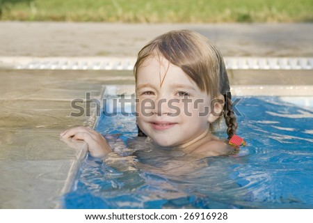 Pretty and cheerful little girl  have a fun and swim in the swimming-pool - stock photo