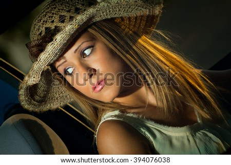 Pretty and sensual blond woman , very elegant , driving a car with hat - stock photo