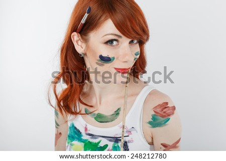 pretty and sexy red haired woman with a paintbrush in her ear over white background