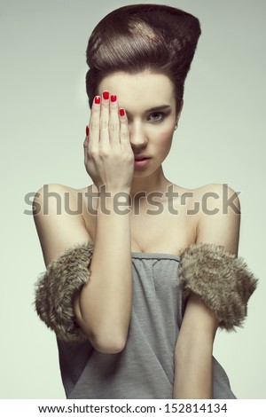 pretty and sexy young girl with creative hairstyle looking in camera and covering one eyes with hand - stock photo