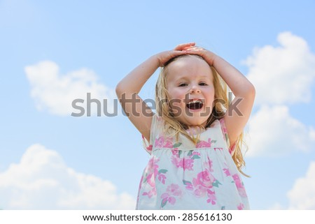 Pretty and smiling blond girl on the background a cloudy blue sky. - stock photo