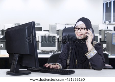Pretty Arabian worker working in the office while wearing headscarf and talking on the mobile phone - stock photo