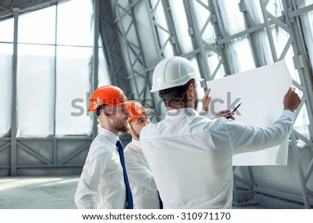 Pretty architect is explaining to builders the plan of construction. He is holding a pen and pointing it at the blueprint with seriousness. The foreman is smiling. Copy space in left side - stock photo