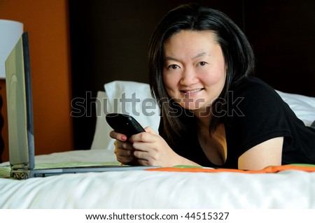 Pretty Asian business woman checks PDA or smartphone in hotel room - smiling at camera