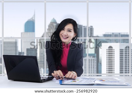 Pretty asian businesswoman smiling at the camera while doing her job with laptop in the office - stock photo
