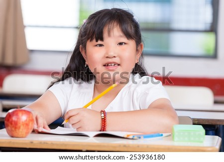 Pretty asian girl at elementary school writing on her book.