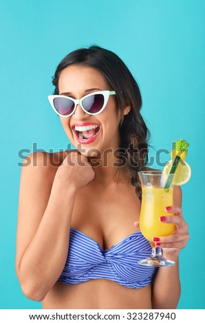 Pretty asian girl having fun,  wearing a bikini and sunglasses holding a cocktail, isolated on bright blue background